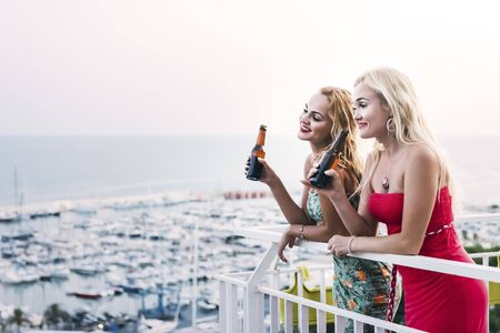 beautiful young girls with beers smiling and having fun at a private party on the outdoor terrace in front of the port, leisure happiness and friendship concept, copy space for text