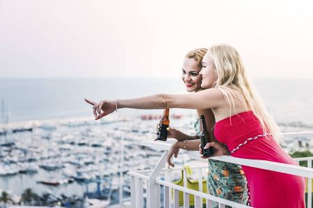 beautiful young girls with beers enjoying and having fun at a private party on the outdoor terrace in front of the port, leisure happiness and friendship concept, copy space for text