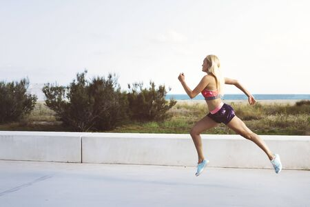 attractive female athlete running for the promenade, sporty blonde woman training, fitness and healthy lifestyle concept, dynamic movement, copy space for text