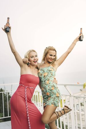 carefree young girls with beers enjoying and having fun at a private party on the outdoor terrace, leisure happiness and friendship concept, vertical photo with copy space for text