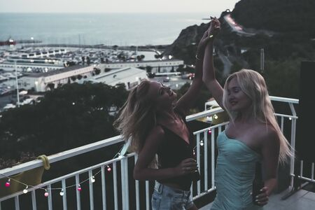 two beautiful young girls with beers dancing and celebrating at a private party on the outdoor terrace at the night, leisure happiness and friendship concept, vintage look with grain Stockfoto