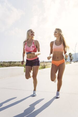 two attractive female athletes running for the promenade, sporty blonde girls training, fitness and healthy lifestyle concept, dynamic movement, vertical photo with copy space for text