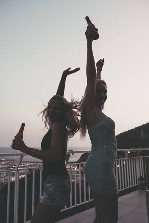silhouette of two beautiful young girls with beers celebrating and having fun at a private party on the outdoor terrace at the night, leisure happiness and friendship concept, vintage look with grain Stockfoto
