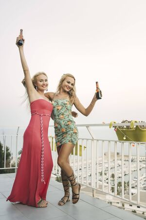 carefree young girls with beers dancing and having fun at a private party on the outdoor terrace in front of the port, leisure happiness and friendship concept, vertical photo with copy space for text Stockfoto