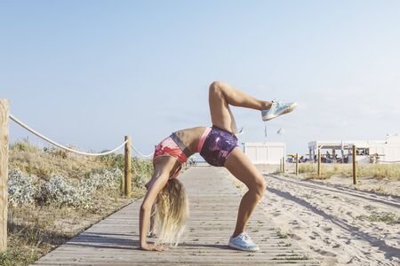 female athlete stretching and doing yoga balance exercises, sports girl doing warm up workout at promenade before training and running, fitness and healthy lifestyle concept, copy space for text