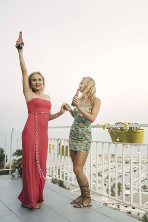 carefree young girls with beers celebrating and having fun at a private party on the outdoor terrace, leisure happiness and friendship concept, vertical photo with copy space for text