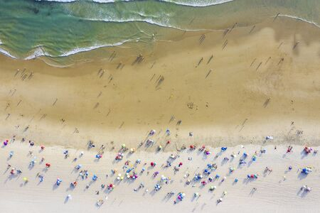aerial view of sandy beach with colorful umbrellas and tourists swimming in beautiful clear sea water at sunny day, top view Фото со стока