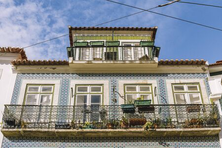 old tiled facade with windows and balcony of historic vintage house with geometric pattern at Lisbon, Portugal