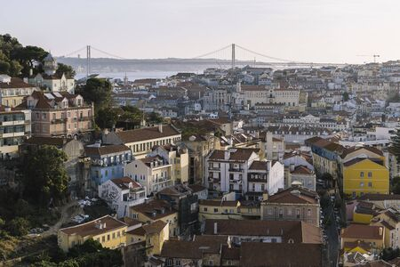 aerial view of Lisbon houses with red roof tiles from Sao Jorge Castle, Vasco Da Gama Bridge at the background Фото со стока