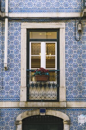 vertical photo of a typical historic vintage house balcony with flowers in an old tile facade with geometric pattern, picturesque architecture at Lisbon, Portugal