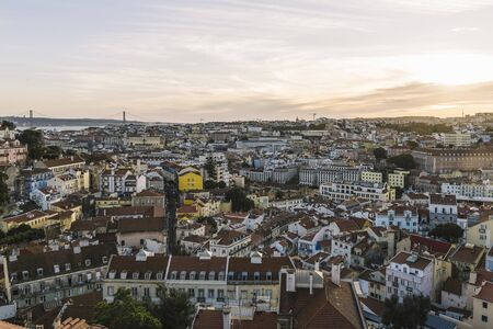 panoramic view of Lisbon houses with red roof tiles from Sao Jorge Castle, Vasco Da Gama Bridge at the background, tourists spots in Portugal