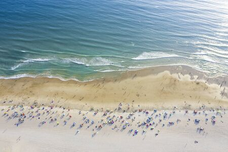 aerial view of sandy beach with colorful umbrellas and lots of tourists swimming in beautiful clear sea water at sunny day, top view