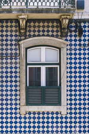 vertical photo of a typical historic vintage house window in an old tile facade with geometric pattern, picturesque architecture at Lisbon, Portugal 写真素材