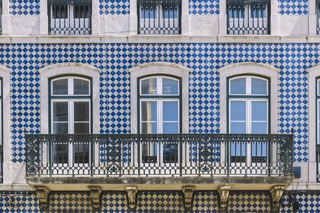 typical historic vintage house facade with windows and balcony in an old tile facade with geometric pattern, picturesque architecture at Lisbon, Portugal