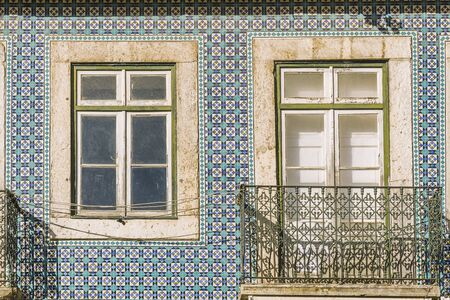 detail of an old tiled facade with window and balcony of historic vintage house with geometric pattern at Lisbon, Portugal