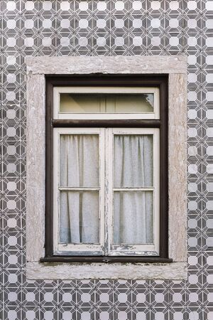 vertical photo of a typical house with vintage wooden window in an old tile facade with geometric pattern, picturesque architecture at Lisbon, Portugal 写真素材