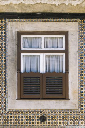 vertical photo of a typical historic old house wooden window in an old tile facade with geometric pattern, picturesque architecture at Lisbon, Portugal 写真素材