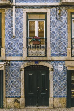 vertical photo of a typical historic vintage house door and window in a old tile facade with geometric pattern, picturesque architecture at Lisbon, Portugal