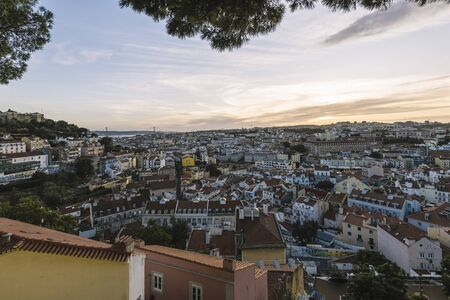 panoramic view of the skyline of Lisbon houses with red roof tiles from Sao Jorge Castle, Vasco Da Gama Bridge at the background, tourists spots in Portugal Фото со стока