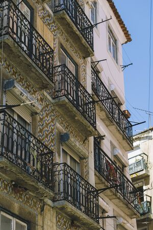 vertical photo of an old vintage tiled facade at Lisbon with windows, balcony and typical portuguese tiles with geometric pattern on the wall, picturesque lisbon architecture
