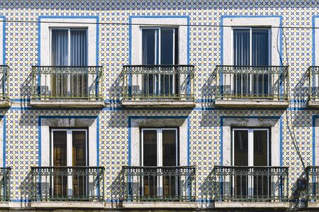 typical vintage tile facade of a portuguese building with windows, balconies and tiles with geometric pattern, picturesque architecture at Lisbon, Portugal