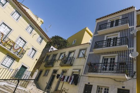 vintage tiled facade at Lisbon with windows, balcony and typical portuguese tiles on the wall, picturesque lisbon architecture