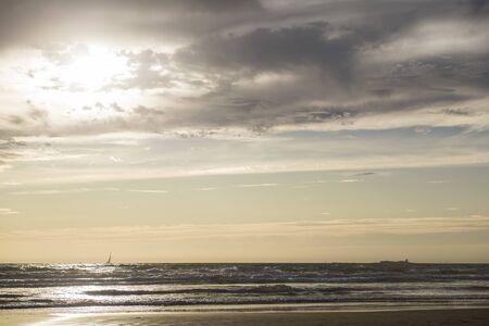 sunset at La Barrosa beach in Sancti Petri, Cadiz, with sailboat sailing towards the castle 写真素材