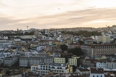 panoramic view of Lisbon houses with red roof tiles from Sao Jorge Castle at sunset, an airplane is flying over at the background, tourists spots in Portugal Фото со стока