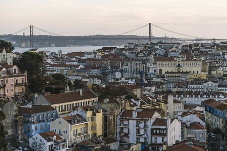 aerial view of Lisbon houses with red roof tiles from Sao Jorge Castle, Vasco Da Gama Bridge at the background, tourists spots in Portugal