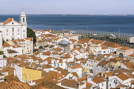 view of historic old district Alfama with river Tagus in the background at sunny day in Lisbon, Portugal, from the overlook of Portas do Sol