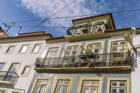 old facade with windows, balcony and typical portuguese tiles on the wall, picturesque lisbon architecture, copy space for text