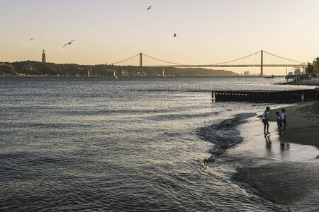 Lisbon, Portugal ? ?? august, 2019: children playing on the banks of the river Tagus at sunset with the red bridge