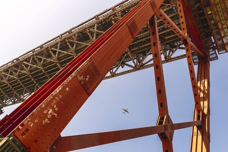 commercial airplane approaching Lisbon seen among the red steel beams of the 25 de Abril (25 April) suspension bridge, travel and tourism concept in Portugal