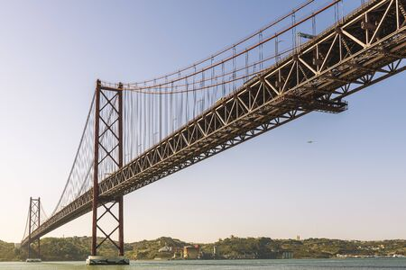 panoramic view of the spectacular 25 de Abril (25 April) suspension bridge over the Tagus river in Lisbon, Portugal. In the background an airplane approaching the city