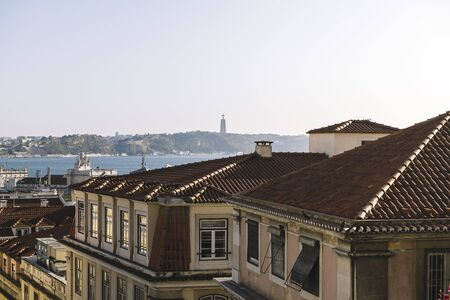 rooftops of the old historical city of Lisbon, Portugal, with the statue of Cristo Rei (Christ the King Statue) in the background, on the other side of the river Tagus.