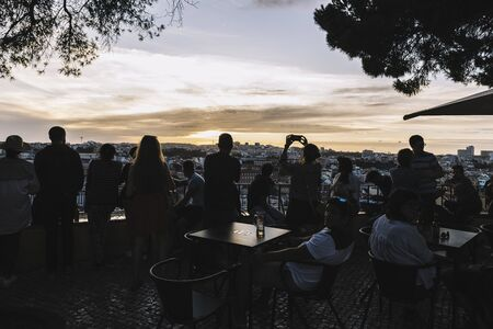 Lisbon, Portugal ? ?? august, 2019: silhouette of tourists looking the cityscape and taking photos with the phone of Lisbon at sunset Фото со стока