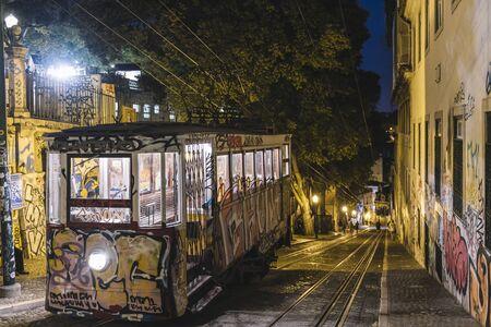 Lisbon, Portugal ? ?? august, 2019: Funicular of Gloria (Elevador da Gloria) painted with graffiti up the Gloria street in the night light