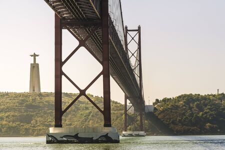 spectacular view of 25 April suspension bridge over Tagus river and Cristo Rei (Christ the King) monument at sunset in Lisbon, travel and tourism concept in Portugal