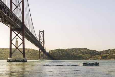 view of 25 April bridge over Tagus river and Cristo Rei (Christ the King) statue in Lisbon, travel and tourism concept in Portugal