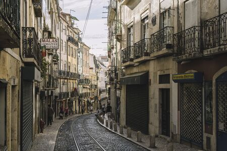 Lisbon, Portugal ? ?? august, 2019: typical traditional portuguese cobblestone street with tramway tracks in Alfama