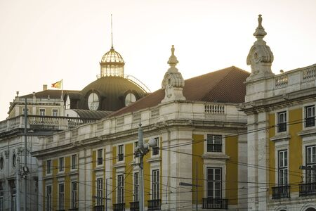 glass dome of the Lisbon City Hall building at sunset with the Portuguese flag waving over the building. In the foreground you can see other old buildings and tramway cables Banco de Imagens