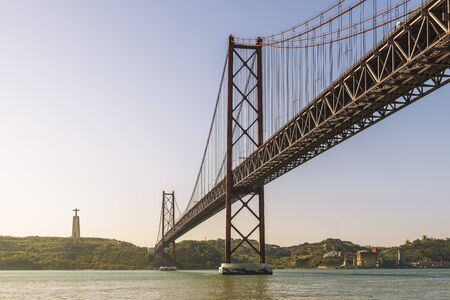 panoramic view of the spectacular 25 de Abril (25 April) suspension bridge over the Tagus river in Lisbon, Portugal. On the other bank you can see the monument of Cristo Rei (Christ the King)