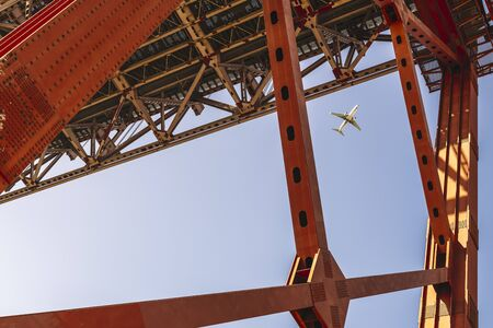 commercial flight approaching Lisbon seen among the red steel beams of the 25 de Abril (25 April) suspension bridge, travel and tourism concept in Portugal