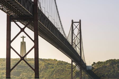spectacular view of 25 April suspension bridge over Tagus river and Cristo Rei (Christ the King) statue in Lisbon, travel and tourism concept in Portugal