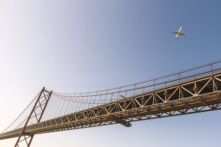 view of the 25 de Abril (25 April) suspension bridge over the Tagus river in Lisbon with an airplane approaching to the city, travel and tourism concept in Portugal Фото со стока
