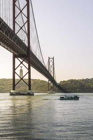 vertical view of 25 April bridge over Tagus river and Cristo Rei (Christ the King) monument in Lisbon, travel and tourism concept in Portugal