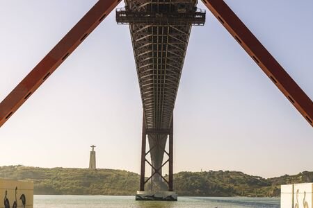 symmetrical view of the 25 April suspension bridge over the Tagus seen from below, on the other bank is the monument Cristo Rei (Christ the King)