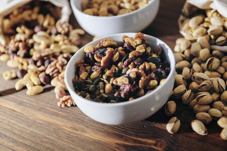 white bowl with mixed nuts, dry fruits and pistachios on rustic wooden table, healthy food and snack concept, copy space for text Banco de Imagens