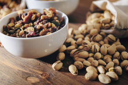 white bowl with mixed nuts, dry fruits and pistachios from a cloth sack on rustic wooden table, healthy food and snack concept, copy space for text