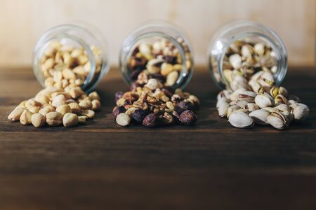 front view of three glass jars with varied nuts and mixed dried fruits inside on a rustic wooden background throwing their contents on the table, healthy food and snack concept, copy space for text
